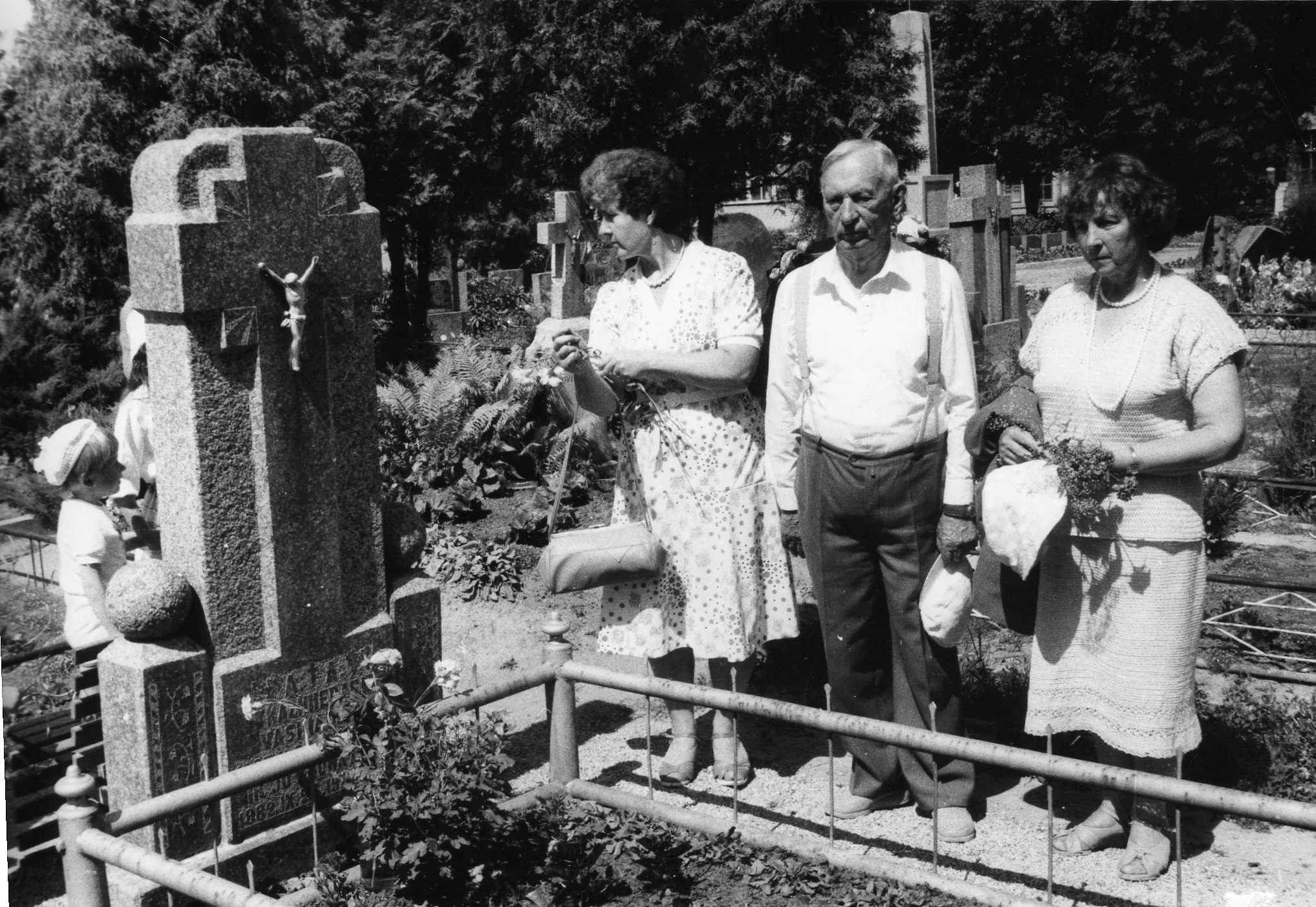 Vasinauskų kapas Pasvalio miesto kapinėse, Stoties g. Prie kapo stovi profesorius, agronomas Petras Vasinauskas su dukterimi Ona Laimute Tindžiuliene (Vasinauskaite) (pirma iš dešinės). 1989 m.
