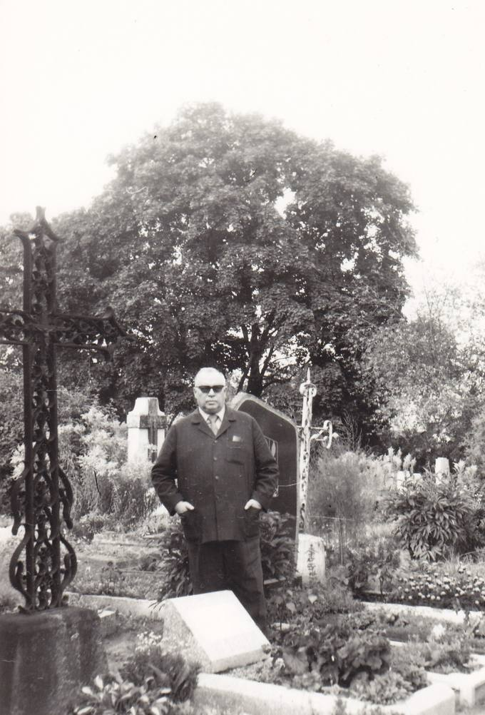 Poetas Eugenijus Matuzevičius prie tėvo Viliaus Matuzevičiaus kapo Biržų kapinėse